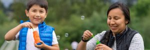 A photo of a family blowing bubbles at the park.