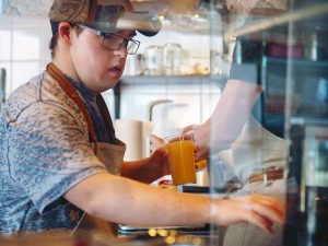 A photo of someone making a coffee for a customer at a coffee shop.