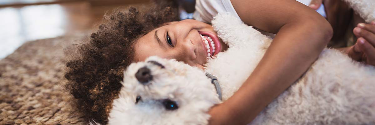 A kid laying down and laughing with her white dog.