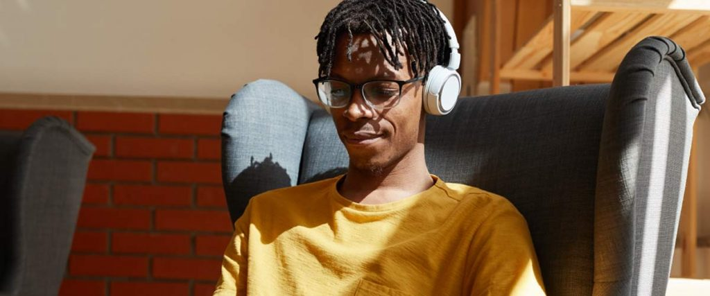 A man sitting in a chair, looking down at something while listening to headphones.